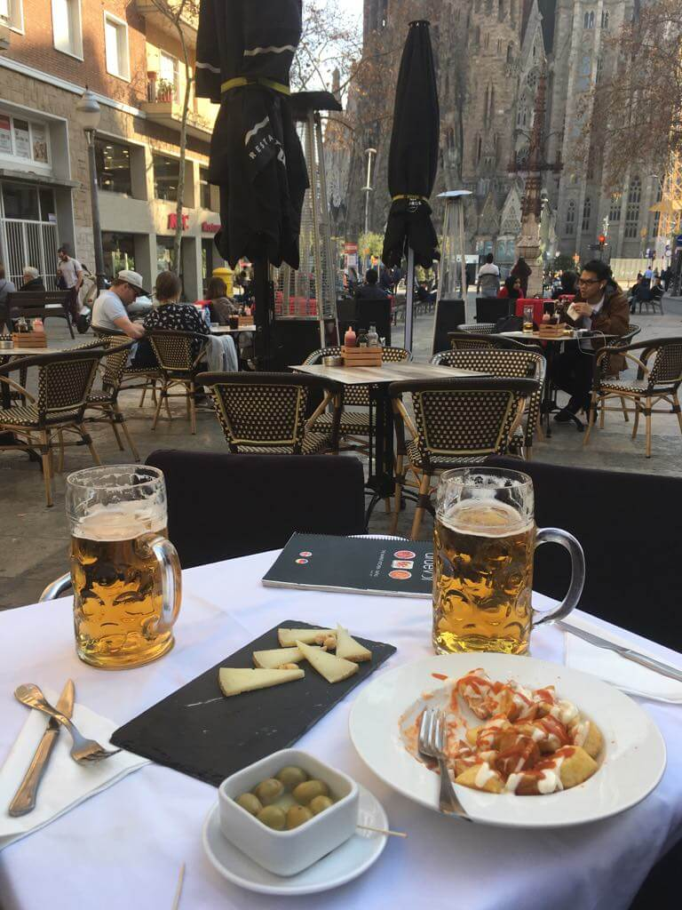 Beer and Spanish tapas on table in foreground. Sagarada Familia in the background