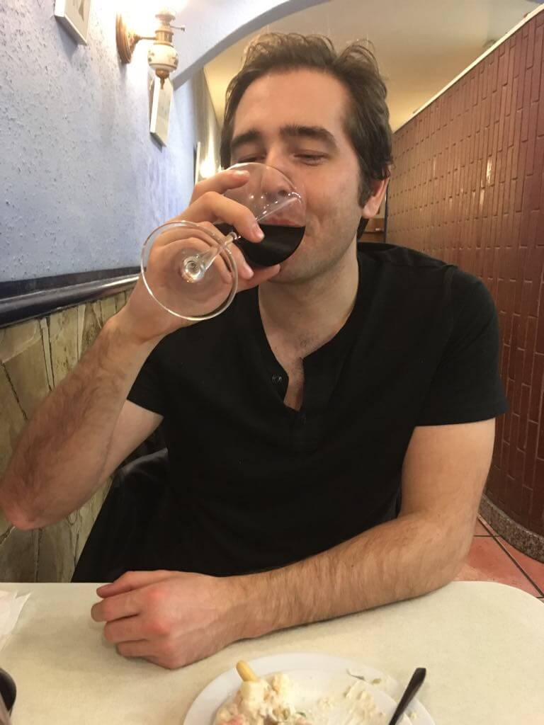Adam drinking a glass of red wine in Barcelona