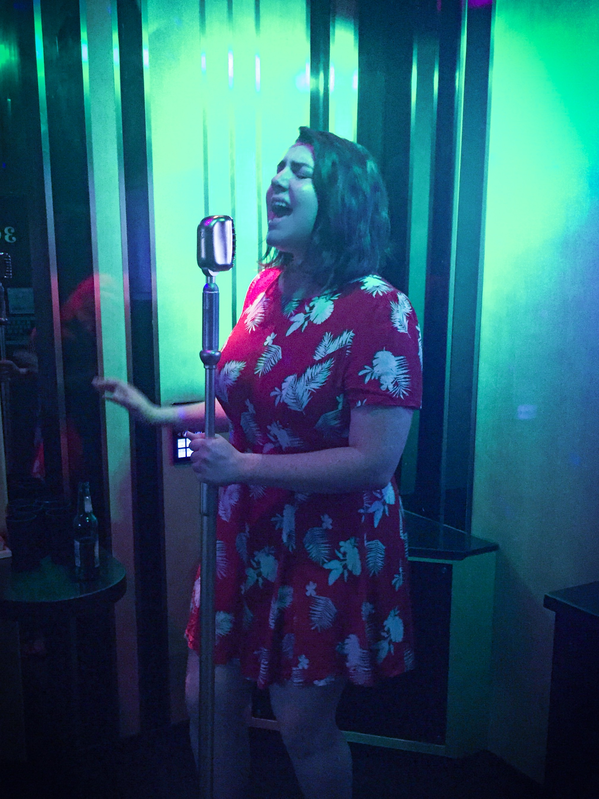 Rose singing with a microphone in a KTV room.