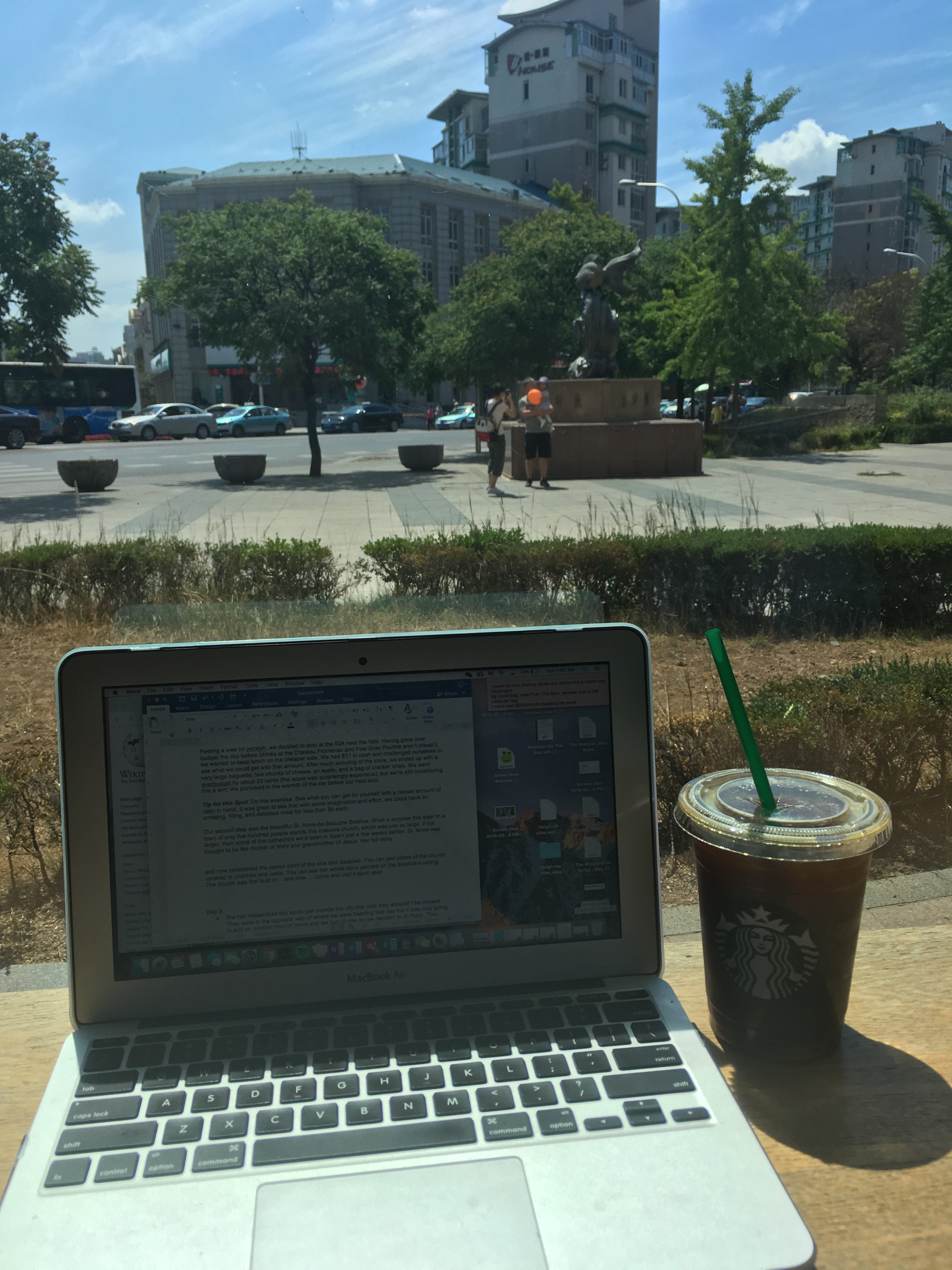 Laptop and iced coffee by the window. View of a little square outside in the background. Dalian, China.