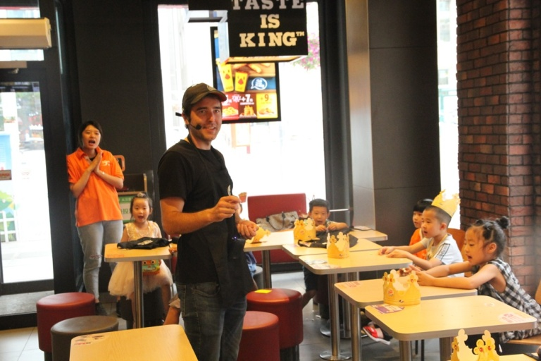 Adam showing a card to children in the English class in Burger King.