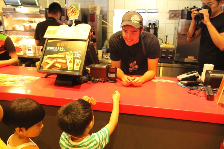 Adam behind the counter at Burger King talking to Chinese children.