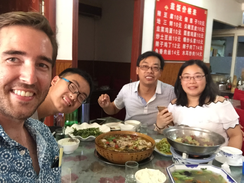 Adam eating lunch with the Chinese family that took him along.