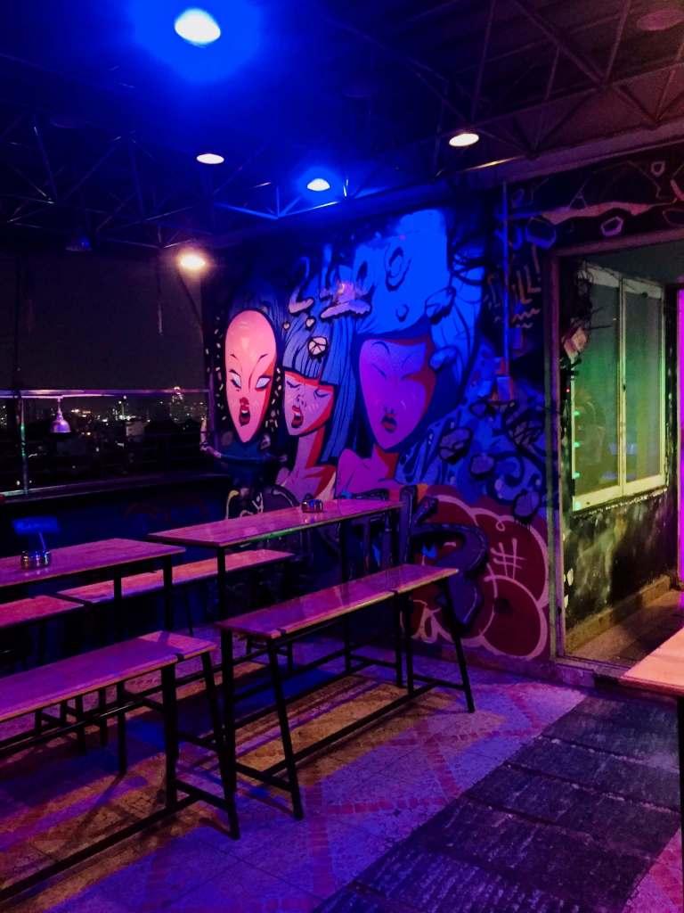 Bar tabletops in front of wall art graffiti.