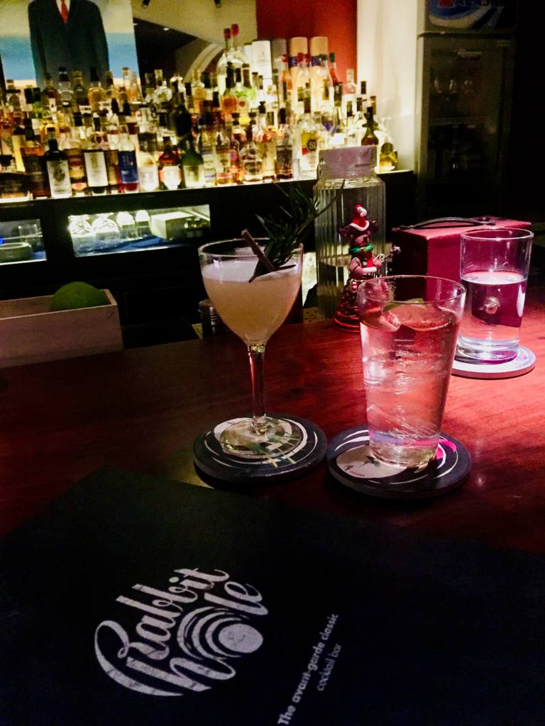 Two cocktails and a Rabbit Hole menu on bar top.