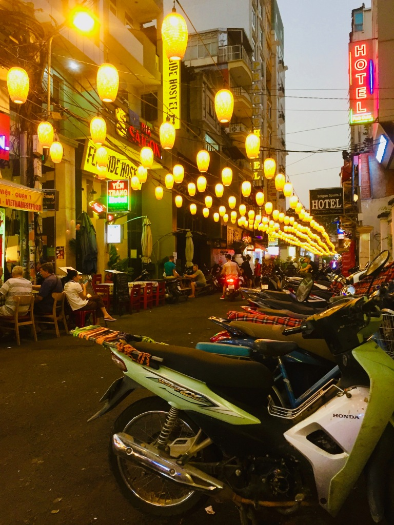 Street with motorbikes and hanging lanterns in Saigon.